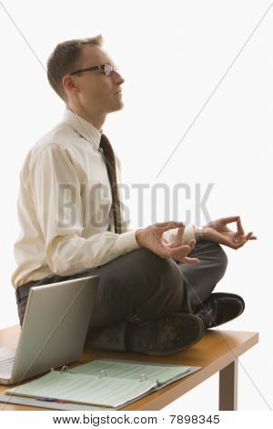 Businessman Meditating on His Desk - Isolated