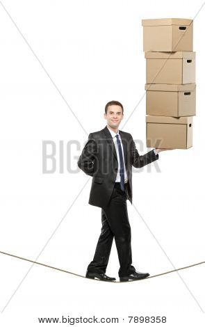 A businessman holding paper boxes and walking on a rope