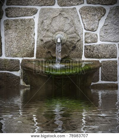 water fountain on a wall made of stones