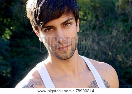 portrait of a beautiful man with bangs wearing a tank top