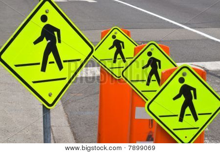 Four Pedestrian Traffic Warning Signs On A Gray Road