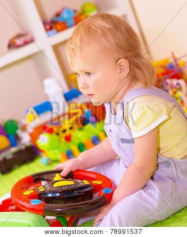 Portrait of cute little baby girl sitting in playing room, play with many colorful toys, spending time in daycare, elementary school, happy childhood concept