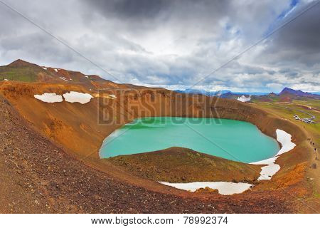 July in Iceland. Lake in the crater of an extinct volcano. Lake water bright green color. On the shores lie snowfields from last year