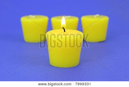 Four citronella candles with one lit