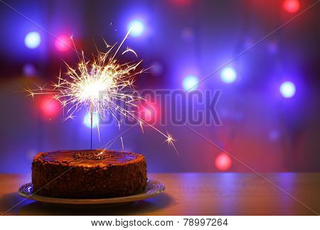 Tasty cake with sparkler on shiny background