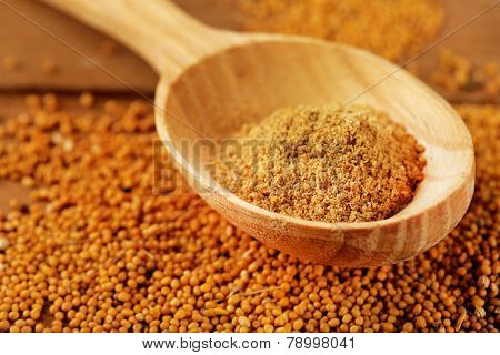 Mustard powder in wooden spoon on mustard seeds, on  wooden background