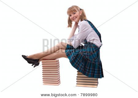Schoolgirl Is Sitting On The Stack Of Book.