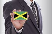 image of jamaican flag  - Businessman in suit holding a business card with Jamaica Flag - JPG