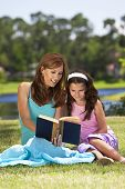 Woman And Girl, Mother And Daughter, Reading A Book Together Outside