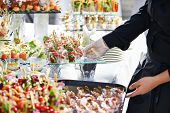 image of waiter  - Waiter with meat dish serving catering table with food snacks - JPG