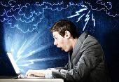 foto of unbelievable  - Young man looking in laptop screen with shock - JPG