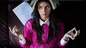 stock photo of exams  - Funny looking brunette woman student trying to study in her room - JPG