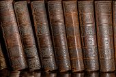 image of leather-bound  - Old Books in a book shelf stacked one next to the other in an upright position - JPG