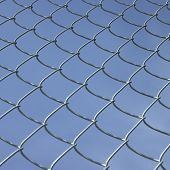 image of chain link fence  - Chain link fence against a perfect blue sky