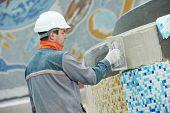 image of overhauling  - industrial tiler builder worker installing floor tile at repair renovation work - JPG