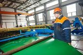 pic of manufacturing  - industrial worker operating metal sheet profiling mechine at manufacturing factory - JPG