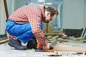 foto of carpenter  - Carpenter worker preparing door frame for indoor installation - JPG