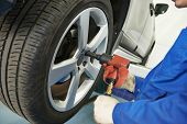 stock photo of adjustable-spanner  - car mechanic screwing or unscrewing car wheel of lifted automobile at repair service station - JPG