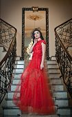 picture of wearing dress  - The beautiful girl in a long red dress posing in a vintage scene - JPG