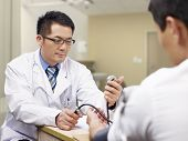 picture of sphygmomanometer  - asian doctor measuring blood pressure of a patient - JPG