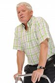 stock photo of zimmer frame  - Disabled casual mature man on white background using walking frame or Zimmer - JPG