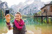 pic of south tyrol  - Happy young woman making selfie on lake braies in south tyrol italy - JPG