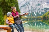 stock photo of south tyrol  - Portrait of happy mother and baby on lake braies in south tyrol italy pointing on copy space - JPG