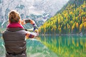 stock photo of south tyrol  - Young woman taking photo on lake braies in south tyrol italy. rear view