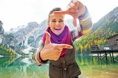foto of south tyrol  - Portrait of smiling young woman on lake braies in south tyrol italy framing with hands - JPG