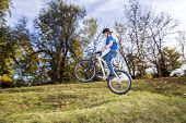 pic of dirt-bike  - teenage boy jumps over a ramp with his dirt bike - JPG