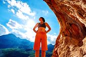 stock photo of cave woman  - girl climber standing in a cave under arch on blue cloudy sky background and looking at the side - JPG