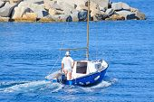 picture of outboard engine  - an old man sailing in Sardinia Italy - JPG