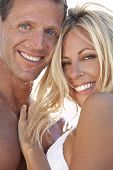 picture of blue eyes  - A sexy and attractive man and woman couple smiling and happy in the sunshine at the beach - JPG