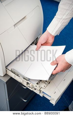 Man Puts The Paper In A Laser Printer