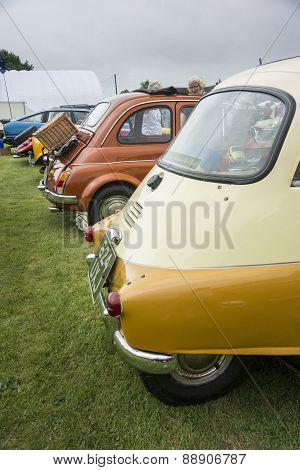 Rear View Of Several Classic Cars In A Line