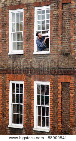 Man painting his window frame