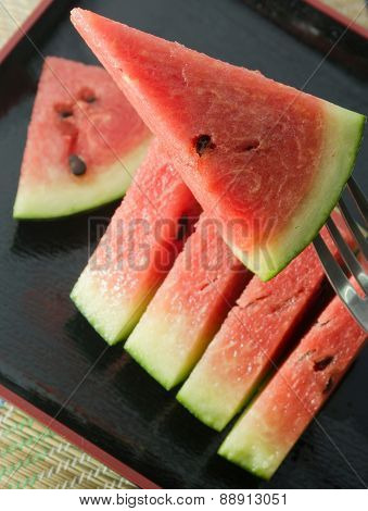 Sliced Of Red Watermelon On A Black Tray