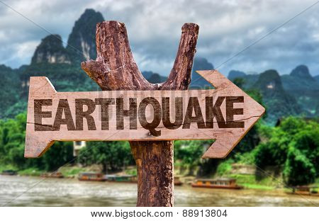 Earthquake wooden sign with countryside background