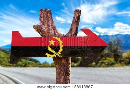 Angola Flag wooden sign with road background