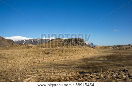 scenic landscape of southern Iceland; of snow-capped mountains, glaciers, grass fields.