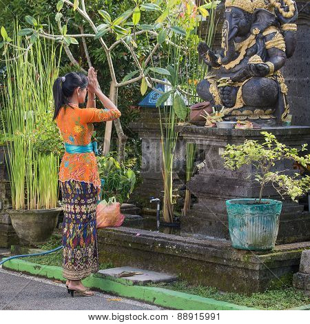 Balinese Woman To Pray Before The Statue Of Ganesha. Bali, Indonesia