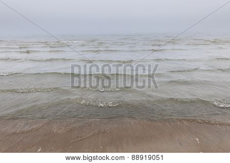 Waves coming to shore on foggy beach with fog over water