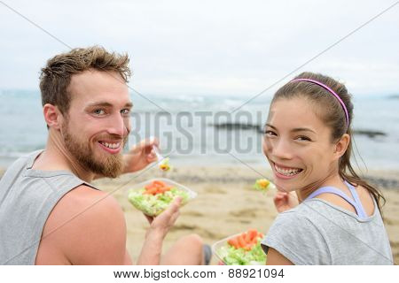 Vegan friends eating vegetarian salad meal during lunch break on beach happy looking at camera. Multiethnic group of young people, Caucasian man, Asian chinese mixed race woman in their 20s.