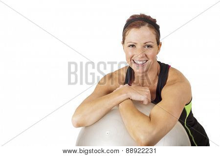 Portrait of a happy, healthy fitness woman leaning on a exercise ball. White background