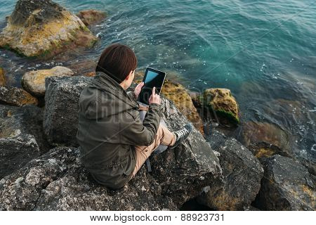 Woman Sitting On Coast With Digital Tablet