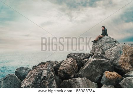 Woman Sitting On Stone Near The Sea