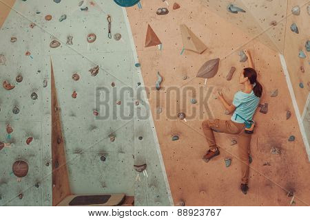 Young Woman Climbing Artificial Boulder In Gym