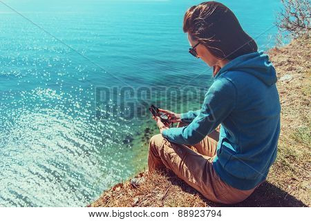 Woman Sitting With A Compass On Coast
