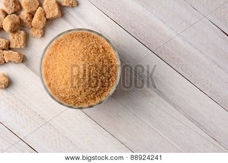 Overhead view of chunks of raw brown sugar and a bowl full of trubinado granules on a white wood table.