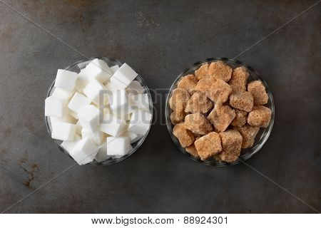 Bowls of sugar cubes. One bowl of raw brown sugar chunks and a second bowl of white sugar cubes. Horizontal format on a used baking sheet.